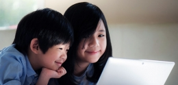 Two Asian children looking at a laptop monitor