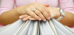 Photo of Hands Folded over a Row of Binders