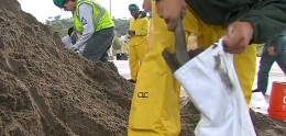 Photos of volunteers filling sandbags