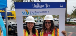 Two smiling women posing inside a handheld frame that says follow the City of San Diego