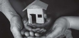 Image of hands holding model of house