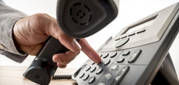 Photo of Close up of Hand Dialing a Telephone