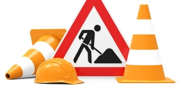 Construction cones, hard hat and a sign showing construction work.