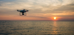 photo of drone flying at sunset