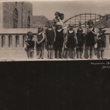 Eight young children at Mission Beach standing at seawall circa 1921