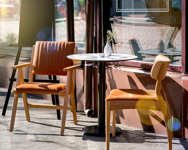 A dining table and chairs on the sidewalk outside a restaurant