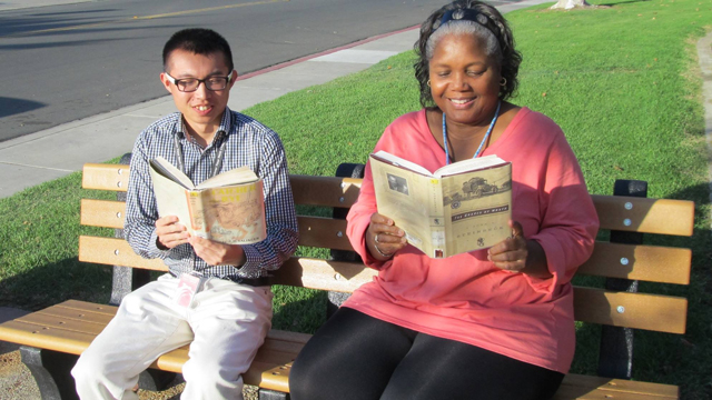 Library patrons reading books in front of the library