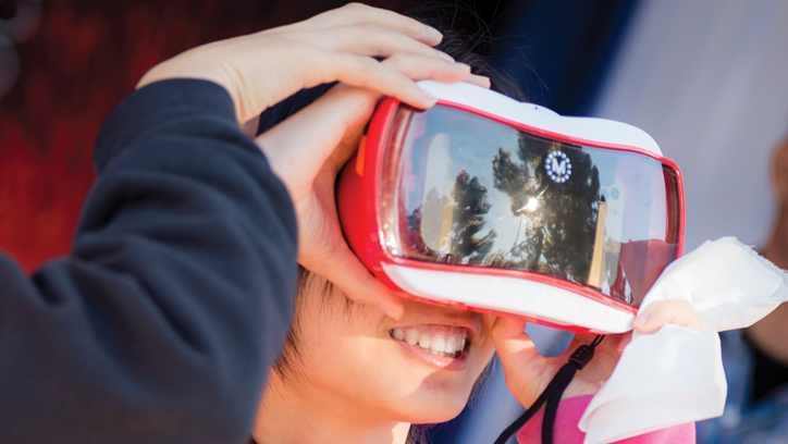 Photo of young girl using virtual reality headset